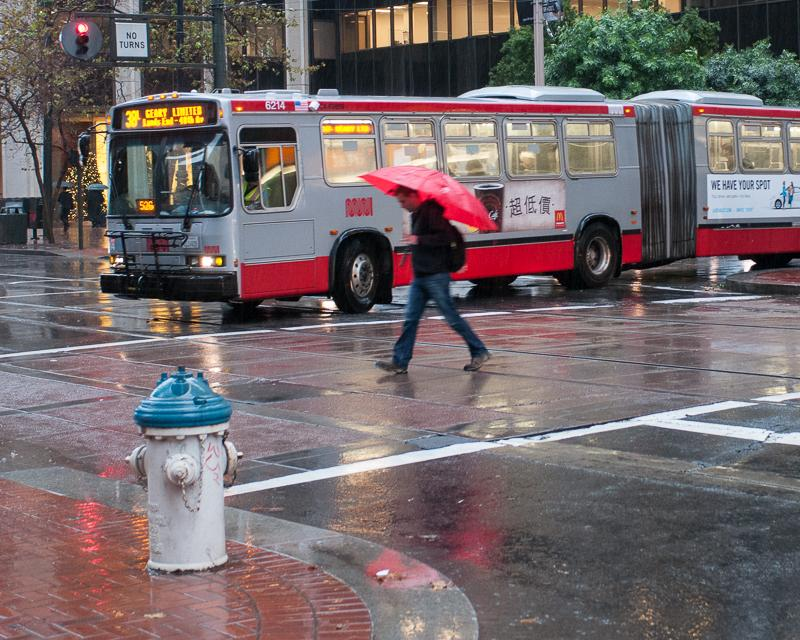 Pedestrian and bus in the rain
