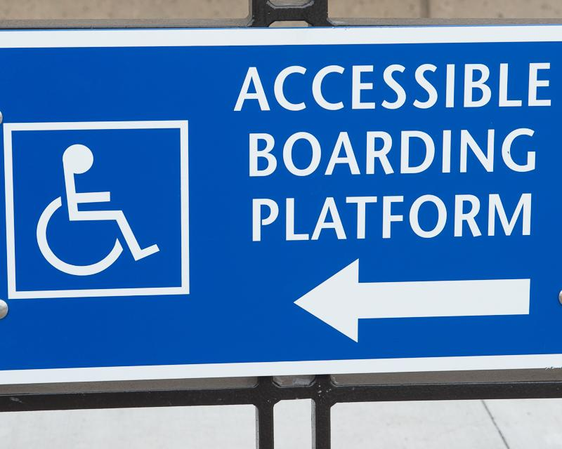 "closeup of blue sign reading ""accessible boarding platform"" with arrow pointing to the left"