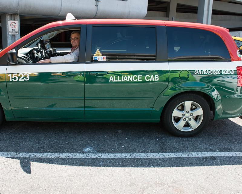 side view of accessible taxi van in green, white and red livery