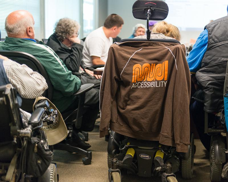 "closeup of people in meeting, one person in a wheelchair has a jacket on the back reading ""Muni accessibility"""