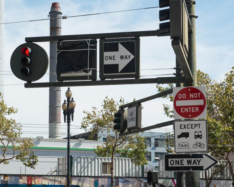 Traffic light and multiple signs, including One Way, Do Not Enter
