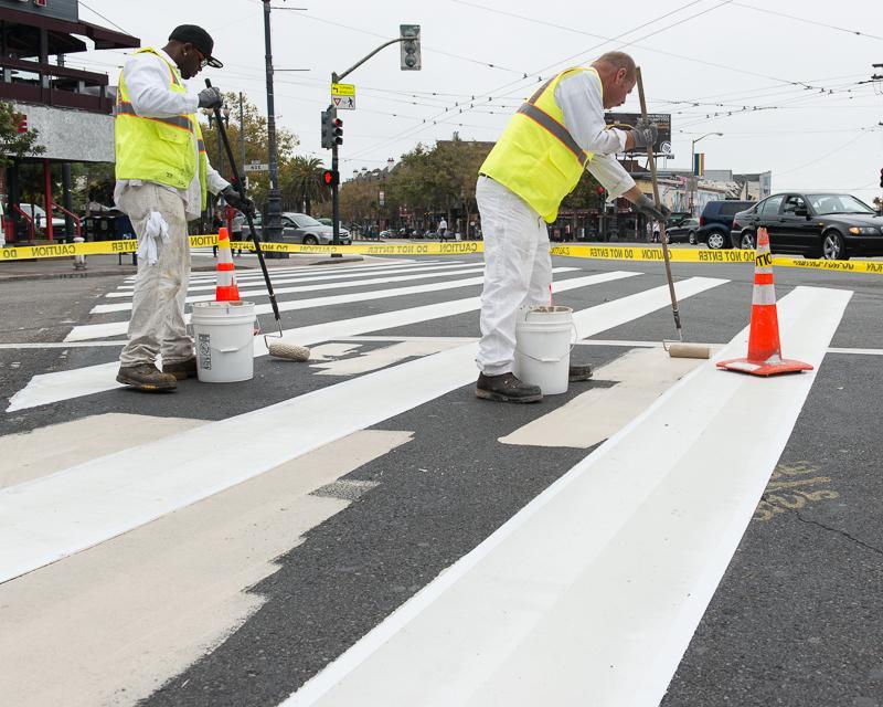 men in safety vests painting crosswalk