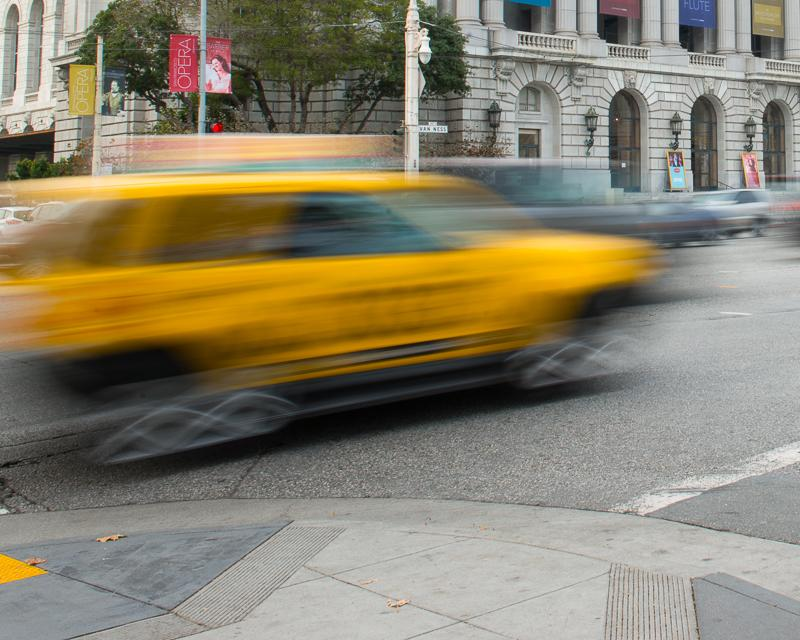 blurred motion photo of taxi driving on van ness