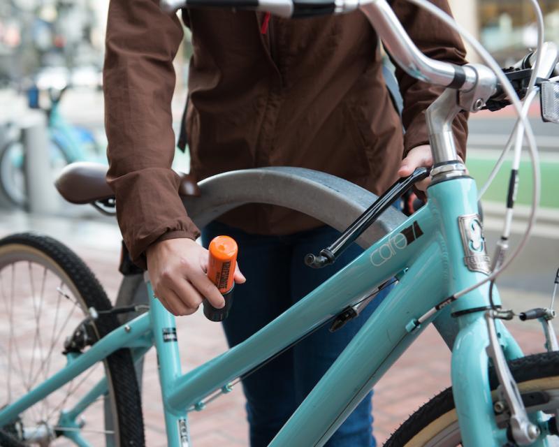 Sidewalk bike rack with teal bike and woman locking it