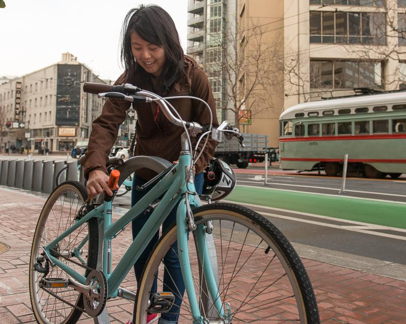 woman locking bike up to bike rack