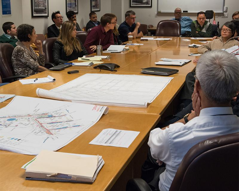 group of people around a large meeting table with papers on table