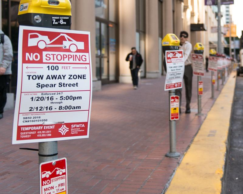 row of parking meters with temporary no stopping signs affixed to them