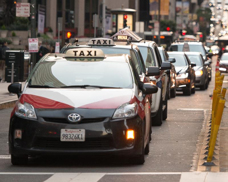 line of taxicabs waiting for traffic light on California Street