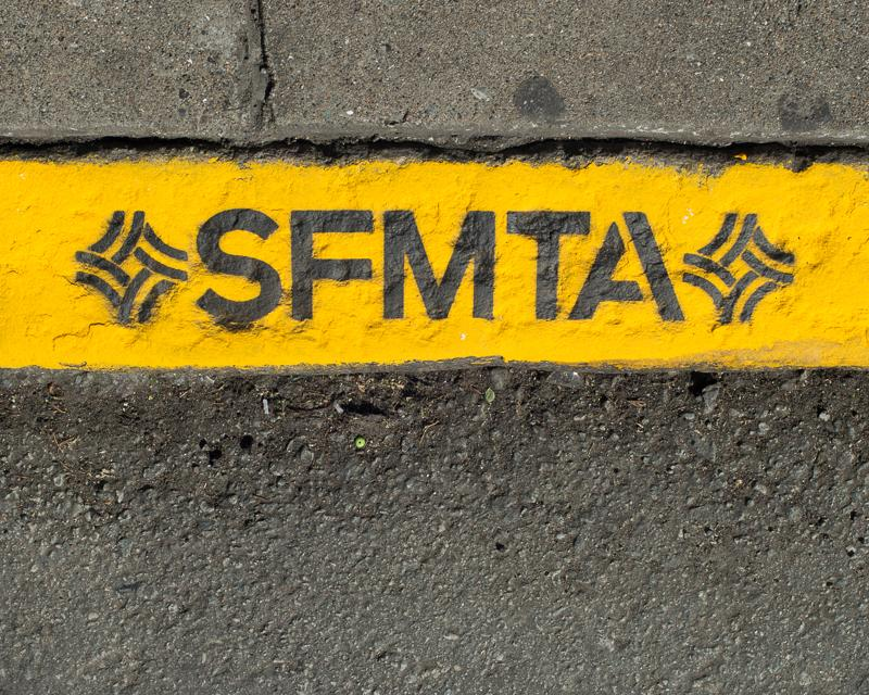 detail view of a yellow painted curb with letters SFMTA and SFMTA logo