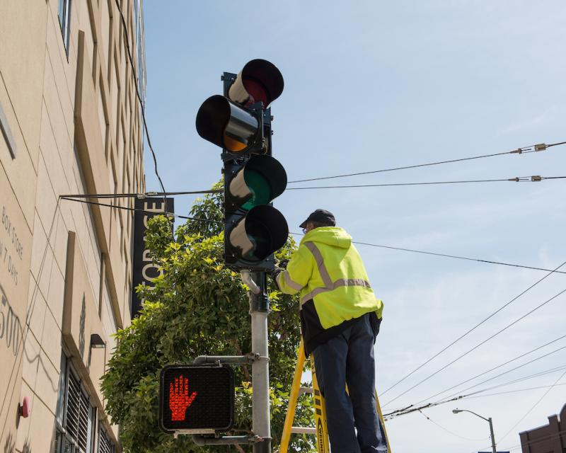 Worker in yellow jacket working on traffic light