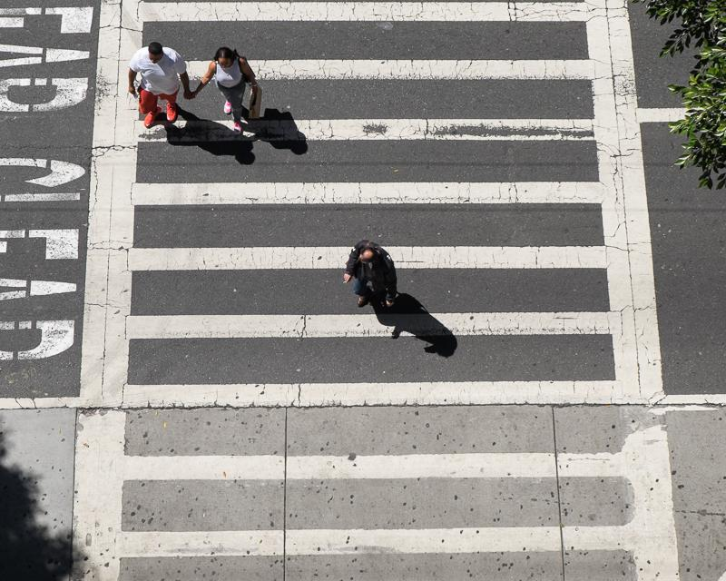 overhead view of striped crosswalk with people crossing