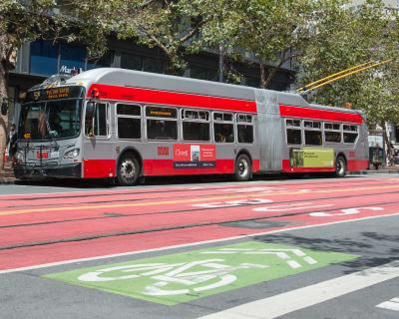 Front 3/4 view of new Muni trolley bus on street.
