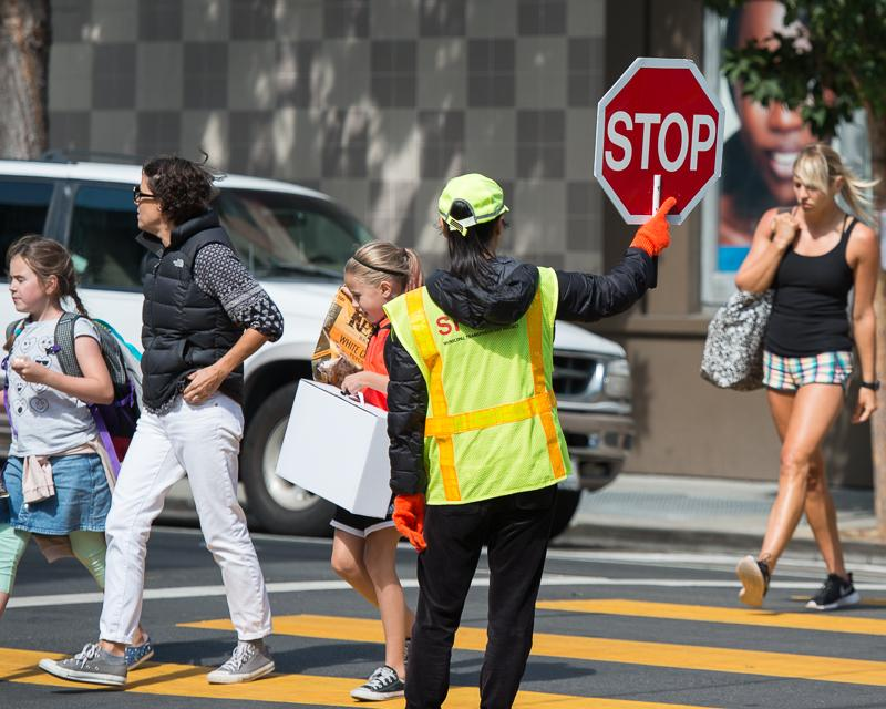 People crossing in crosswalk in front of crossing guard holding stop sign