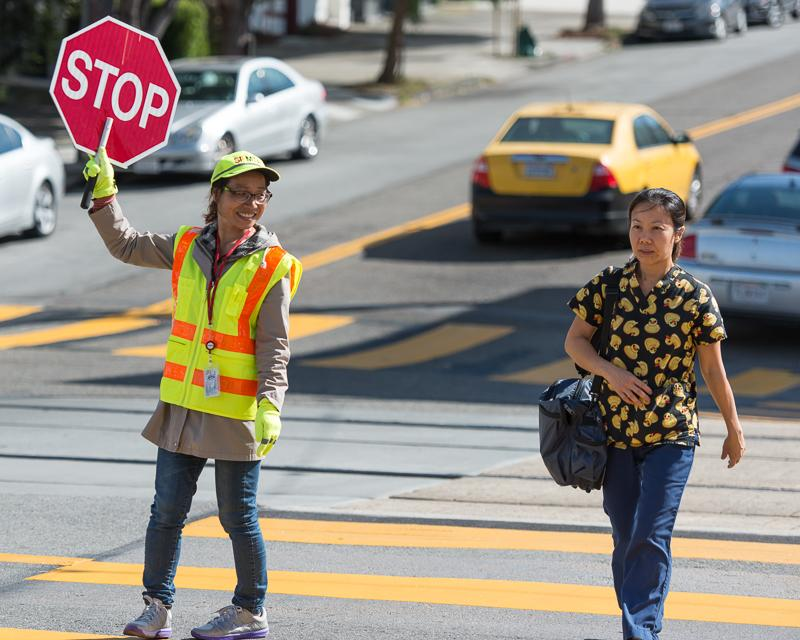 crossing guard helping pedestrians cross intersection