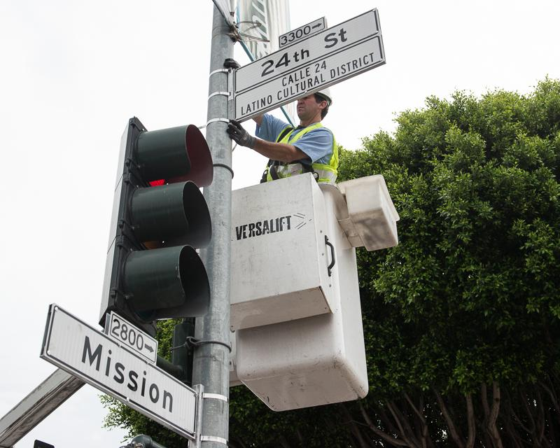 man in bucket truck installing street sign