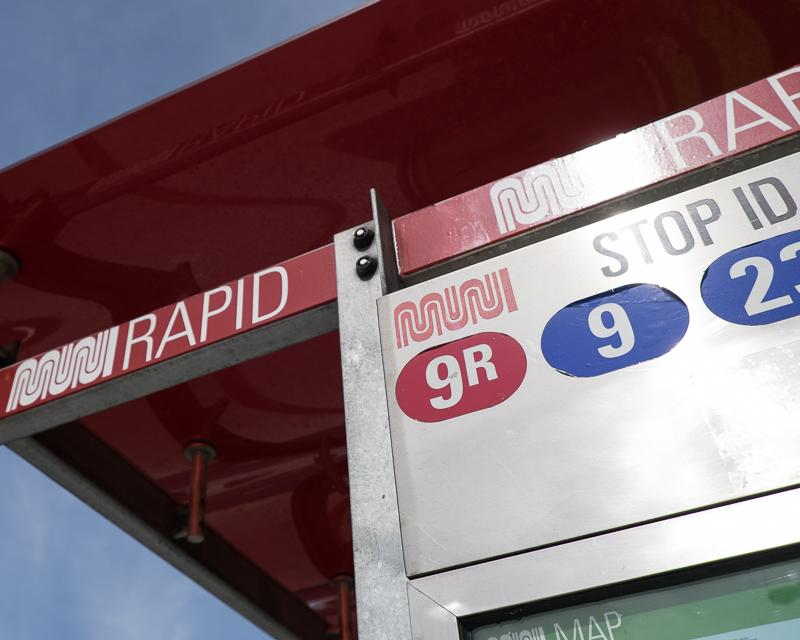 closeup of muni bus shelter with route designation stickers and signage