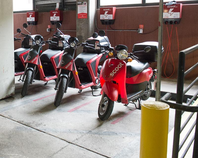 row of red electric rental scooters inside parking garage