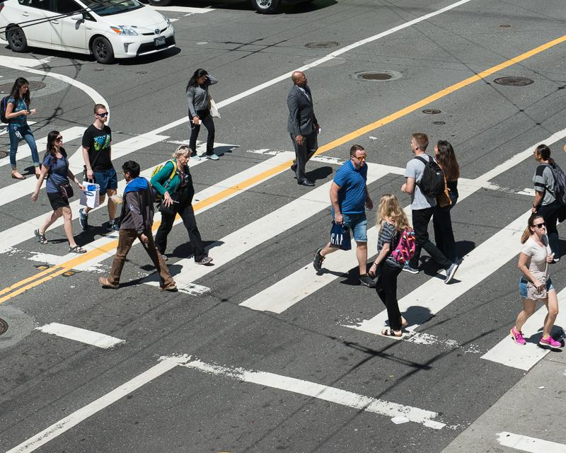 group of people crossing street in striped crosswalk