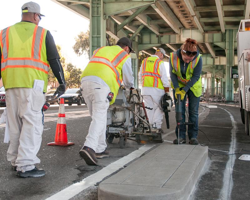 group of painters laying road striping and sign shop worker installing safe hit post on street