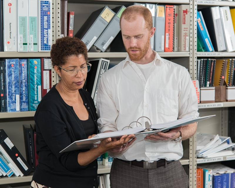 two people looking at a bound report in a library room