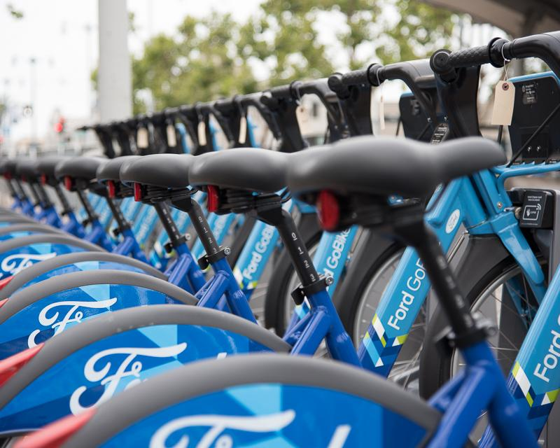 row of blue rental bicycles in ferry plaza
