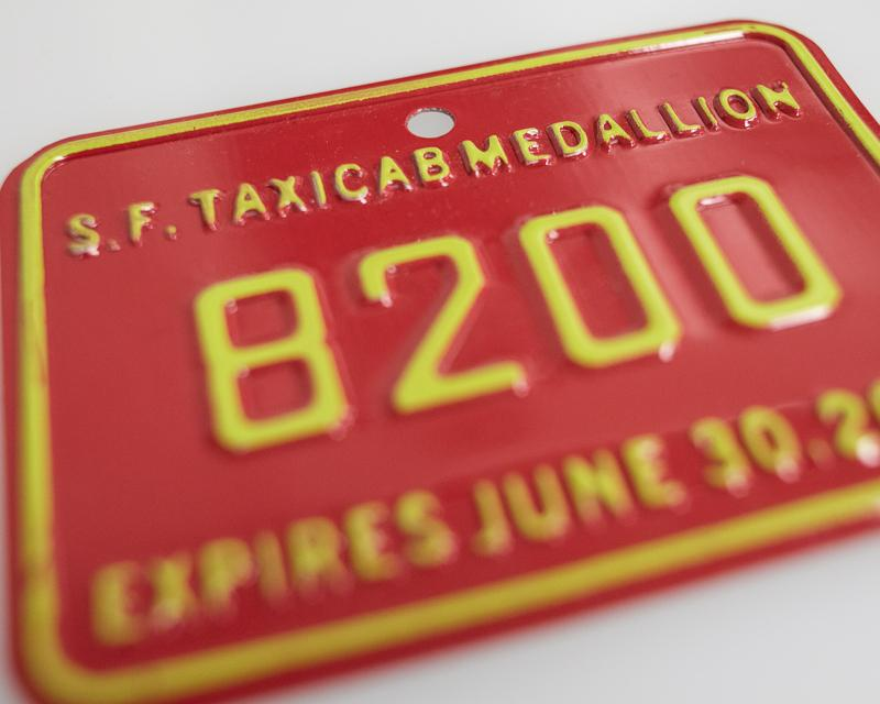 detail view of red and yellow colored taxi medallion plate