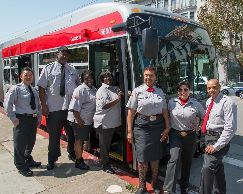 group of transit operators standing with new articulated coach