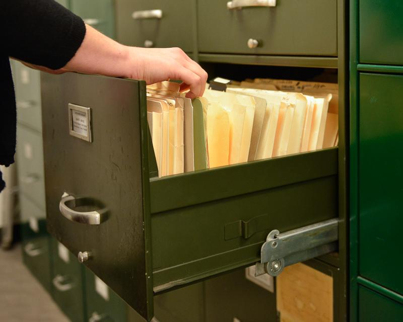 person flipping through files in a filing cabinet drawer