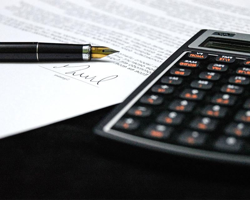 Photo of calculator, paper and pen
