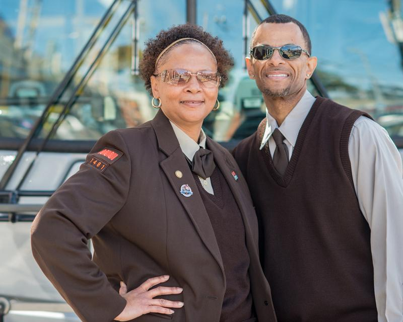 Two Muni drivers in uniform with bus in background.