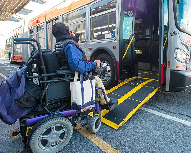 A wheelchair user boards a Muni bus