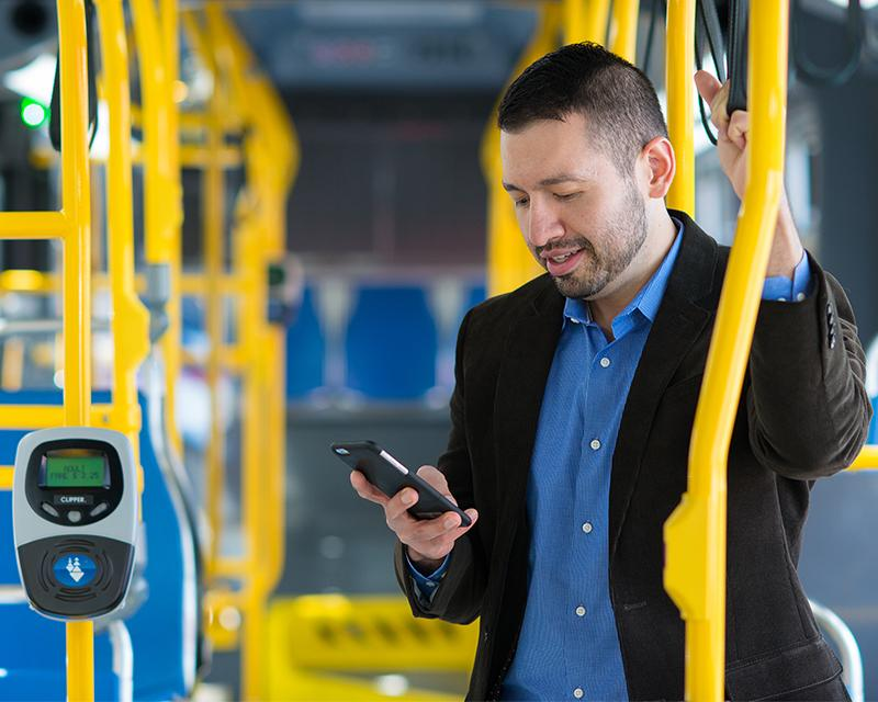 man on bus using smartphone near clipper card reader