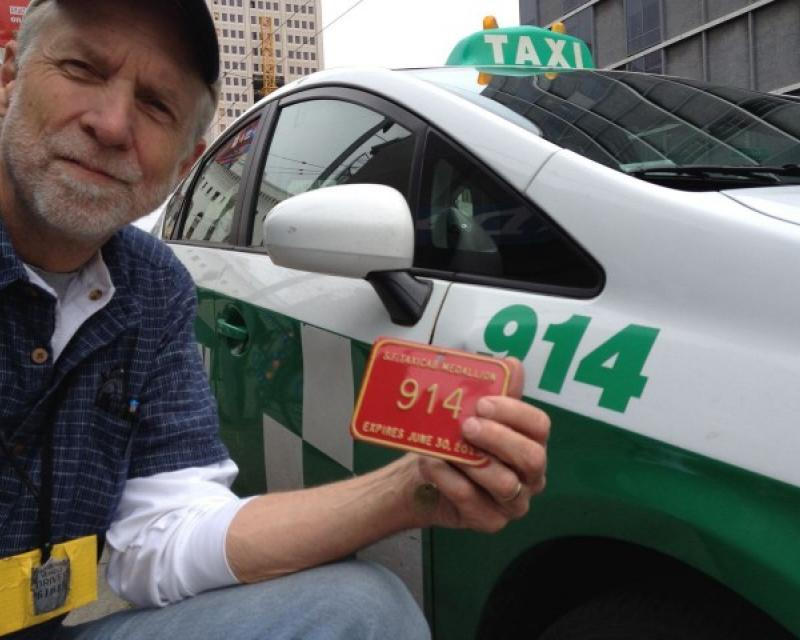 A Taxi driver holding his Medallion