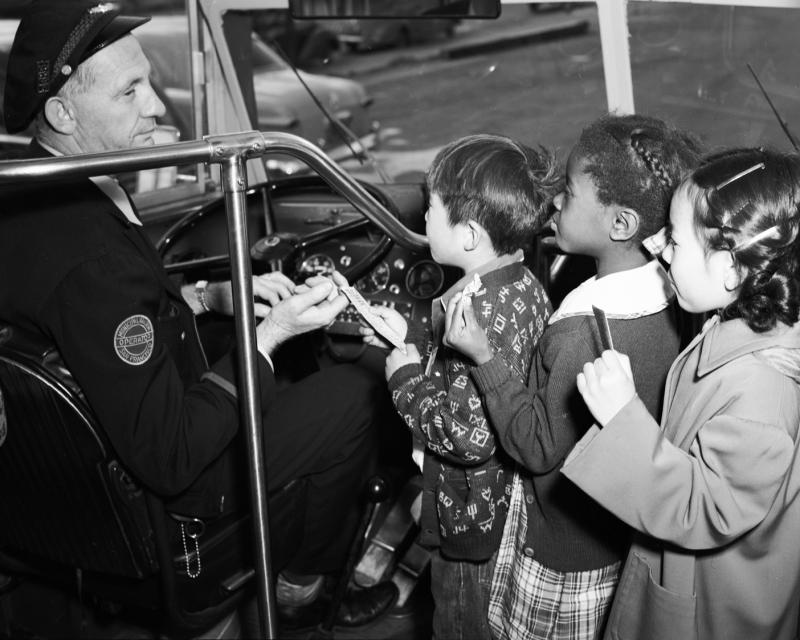 black and white photo of three children receiving transfers from Muni driver