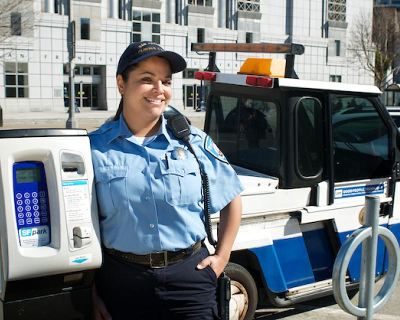 Image of a parking control officer standing by a meter