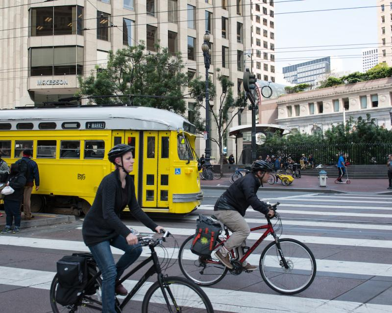 Two people riding bikes alongside a historic streetcar