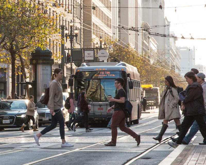Image of a Muni Bus on Market with pedestrians in the foreground