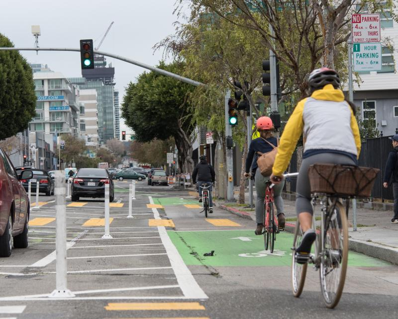 People riding a bike on the newly reconfigured Folsom Street