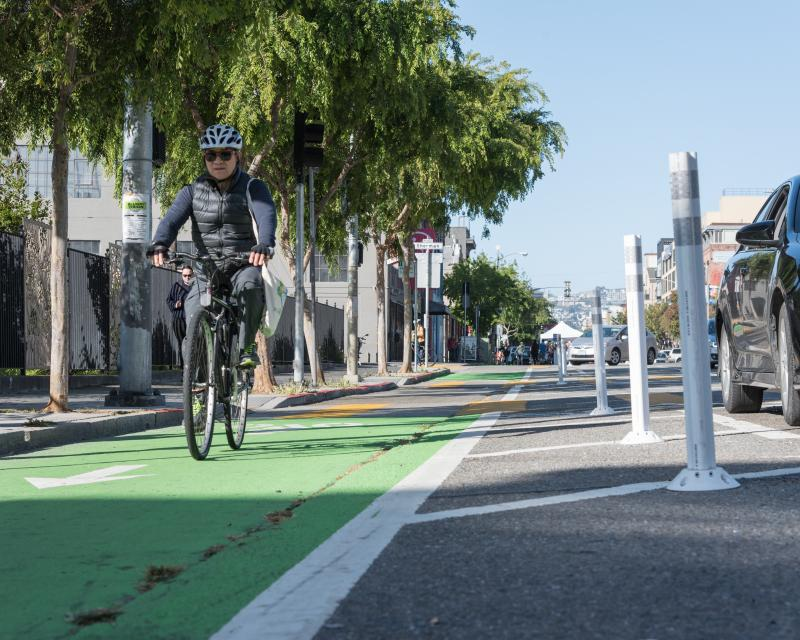A man riding a bike on the parking-protected bikeway on Folsom Street