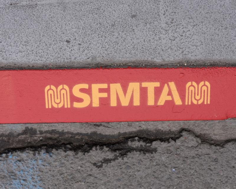 closeup of red color curb with letters SFMTA and new M logo