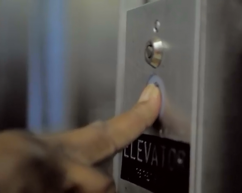 A customer pushes a call button to request an elevator