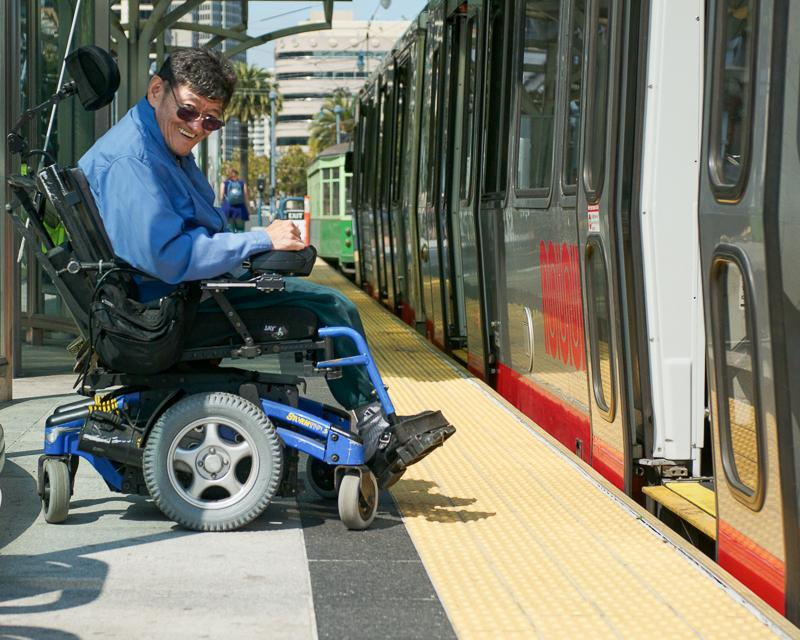 man in a wheelchair on boarding platform in front of open train doors, smiling and looking at the camera