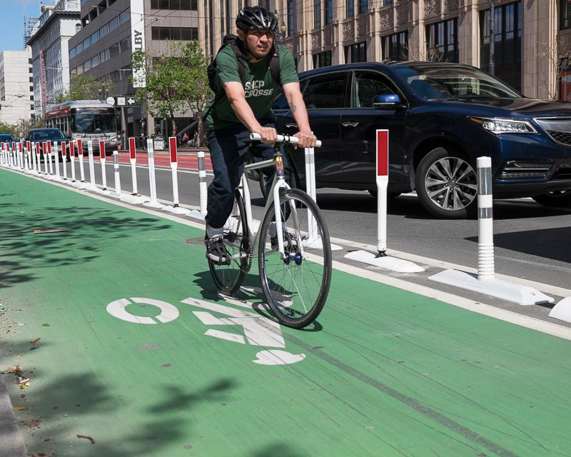 person riding bike in protected bike lane on market