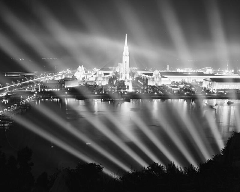 A view of Treasure Island and the brightly lit fairgrounds taken from Yerba Buena Island at night circa 1939.
