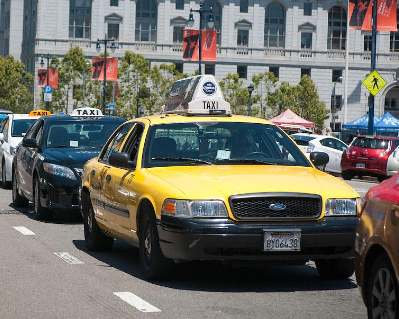a row of taxis along Polk Street with the state office building in the background