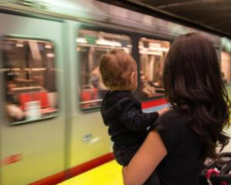 Mother holding a baby on a Metro platform as a train passes by