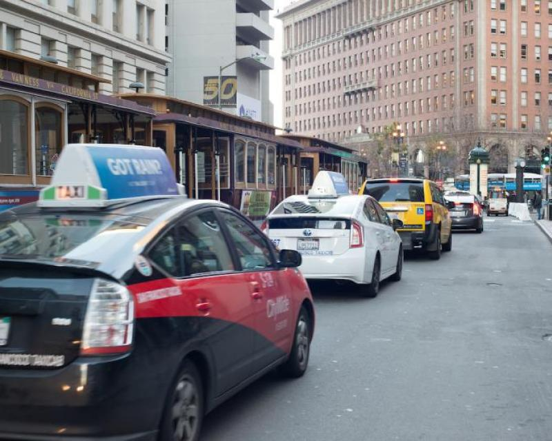 Taxis from various companies, lined up on California street alongside cable cars
