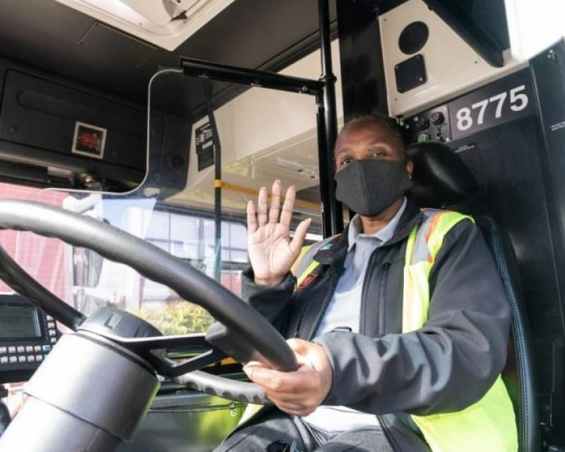 Operator wearing a mask and waving from driver's seat