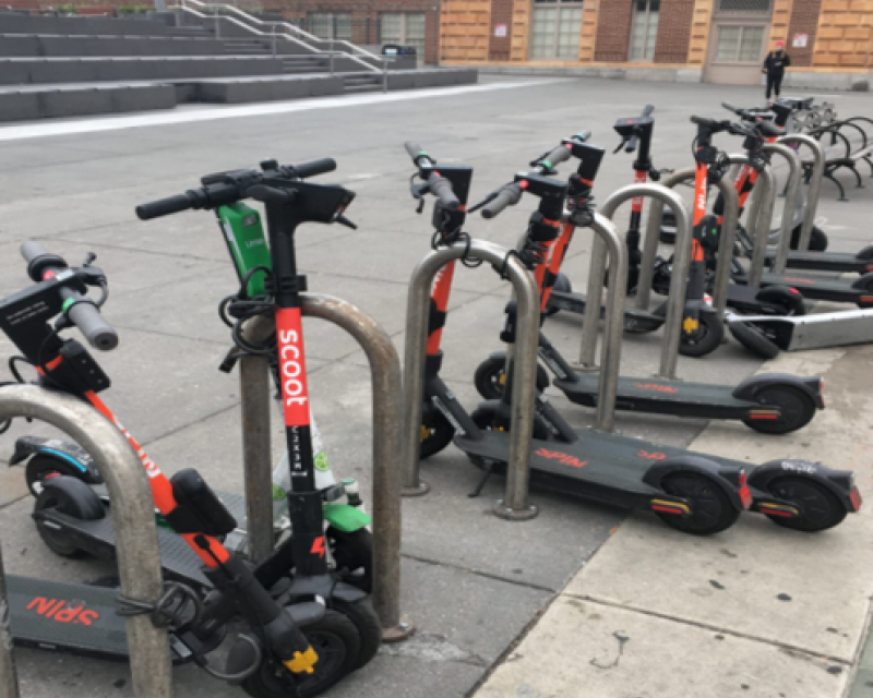 Scooters parked at bike racks