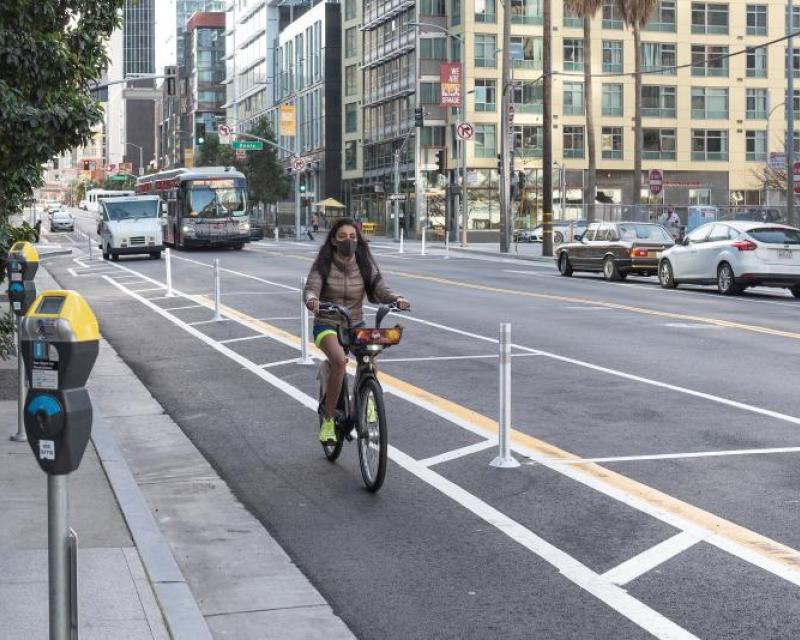 Image shows woman biking down new protected bike lane